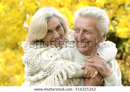 nice old couple standing in autumn park - stock photo