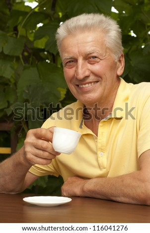 Nice older man sitting at a table at home on the veranda
