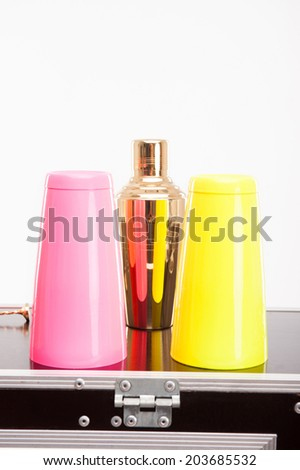 Nice orange shaker with pink and yellow glasses standing on the bar counter - stock photo