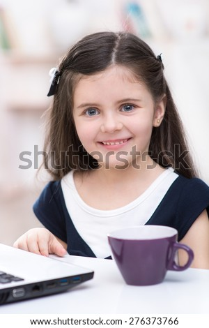 Nice picture of little dark-haired girl. Girl sitting at table with cup and laptop, smiling and looking at camera. Room interior as a background - stock photo