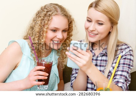 Nice picture. Two attractive smiling ladies sitting in cafe and looking at mobile phone.