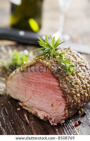 nice piece of roasted sirloin beef covered in herbs - stock photo