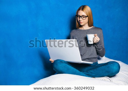 Nice portrait of beautiful girl on blue background. Young woman with glasses sitting cosily, holding cup of coffee and using laptop - stock photo