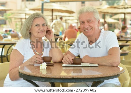 Nice senior couple with coffee sitting on the table on vacation