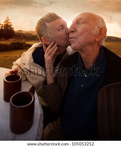 Nice senior woman kisses her husband outside - stock photo