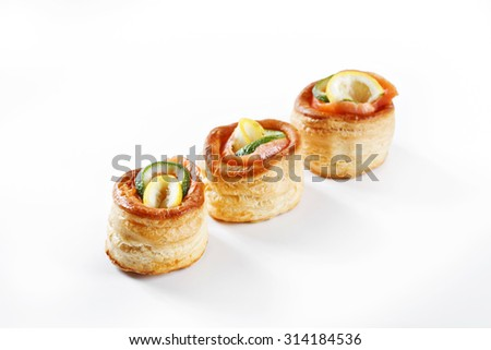 nice set of rolled pancake canapes with lemon, lime and salmon on white background studio isolated with space for text template - stock photo