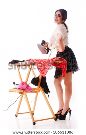 Nice, sexy and happy pin up girl ironing - stock photo
