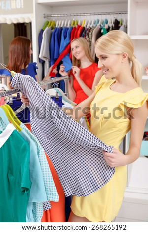 Nice shirt. Vertical shot of a smiling young girl taking a plaid shirt from a clothing rack in a fashion store