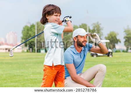Nice shot! Confident little boy playing golf while his father standing close to him on the golf course - stock photo