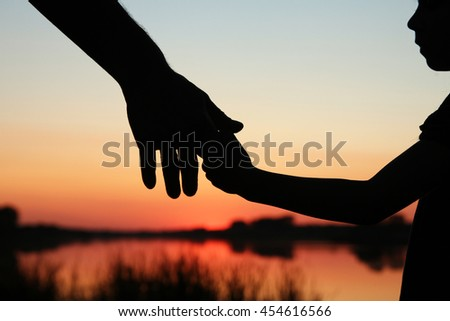 nice silhouette parent and child hands - stock photo