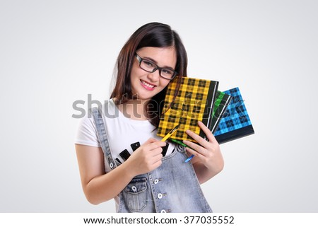 Nice smiling Asian school girl wearing nerd glasses, posing with some books and pen, on white background - stock photo