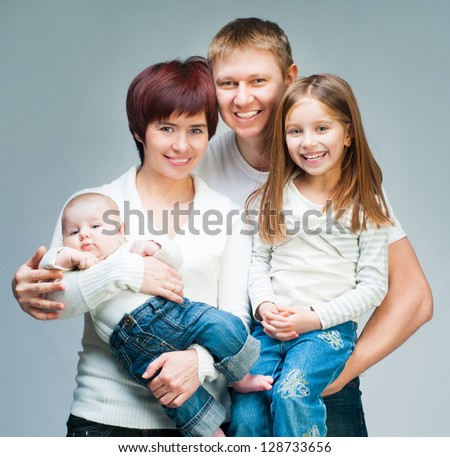Nice smiling family looking at the camera - stock photo