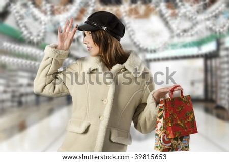 nice studio shot of cute girl with winter dress and black hat with shopping christmas bags