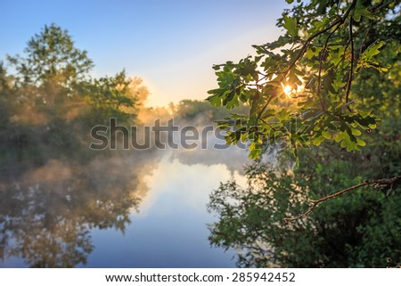 Nice sunrise landscape over river with morning fog - stock photo