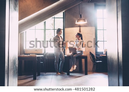 Nice talk with colleague. Cheerful young man and woman discussing something and smiling during their coffee break in creative office