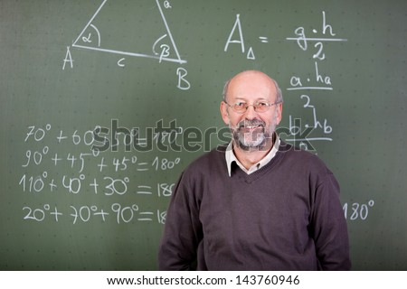 Nice teacher smiling at camera in his classroom - stock photo