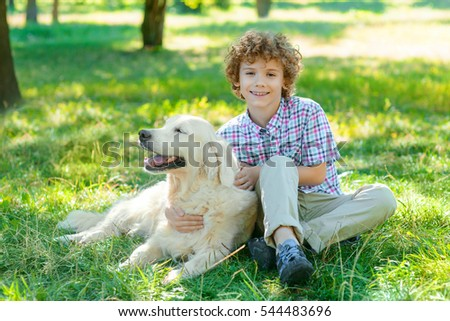 Nice time with a golden retriever for one lovely redhead boy sitting on the green grass in the park. Positive emotions of an animal and a human.