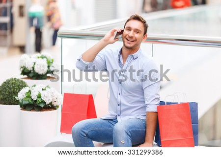 Nice to hear you. Blissful smiling handsome young father sitting on the bench and talking on mobile phone while having shopping