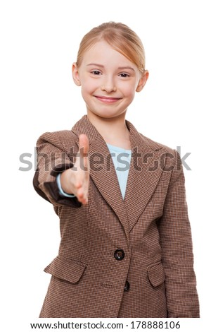 Nice to meet you! Cheerful little girl in formalwear stretching out hand for shaking while standing isolated on white - stock photo