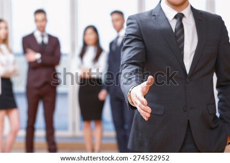 Nice to meet you.  Young business man standing in foreground extending hand for a handshake, his co-workers discussing business matters in the background - stock photo