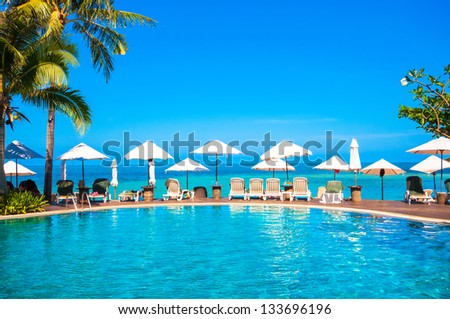Nice tropical pool beside the sea, summer time - stock photo