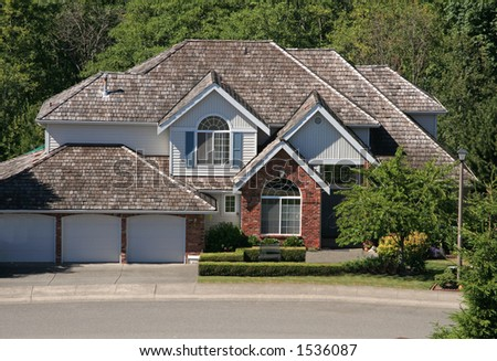 "Nice two-story three-garage house amidst green vegetation. ""Dream home"" from real-estate viewpoint. - stock photo"