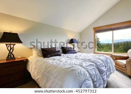 Nice upstairs bedroom with vaulted ceiling and carpet floor.White double bed with black pillows and decorative light  lamps beside the bed - stock photo