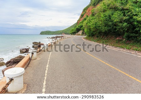 nice view of the road curve and pole beside sea beach and mountain  - stock photo