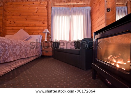 Nice warm interior of mountain lodge apartment with detail of fireplace. Fox Glacier Lodge, Fox Glacier, West Coast, South Island, New Zealand. - stock photo