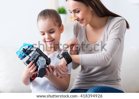 Nice weekend. Cheerful  delighted smiling mother and her cute daughter sitting on the couch and playing with robot while having fun - stock photo