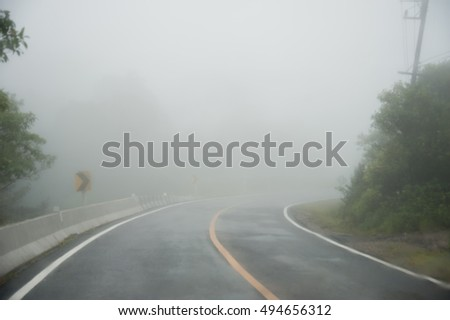Nice winding road caught in the fog in winter time