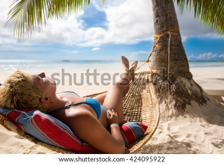 nice woman in hammock in tropical environment - stock photo