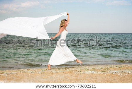 Nice woman jumps on the beach