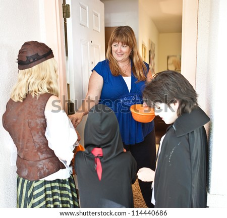 Nice woman passing out Halloween candy to trick or treaters at her door. - stock photo