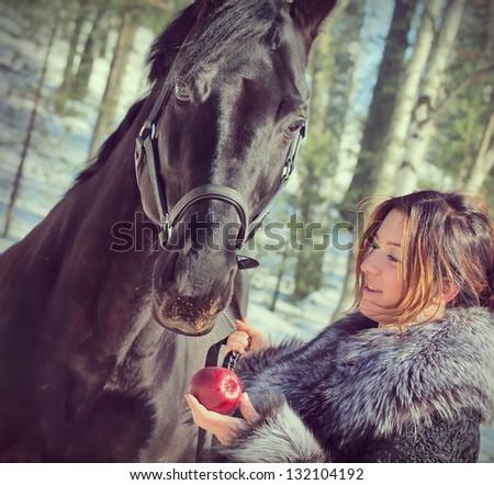 nice women with black horse portrait. - stock photo