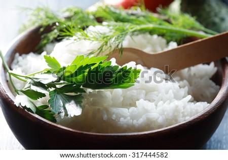 Nice wooden bowl fool of boiled rice on dark background - stock photo