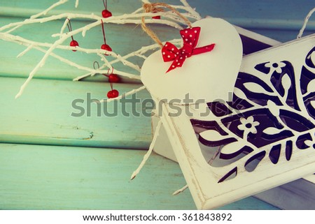 Nice wooden casket with paper heart Valentines day card on blue board. - stock photo