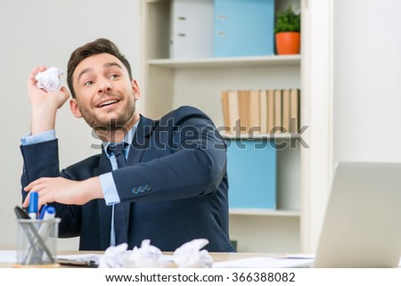 Nice worker playing with paper at the table  - stock photo