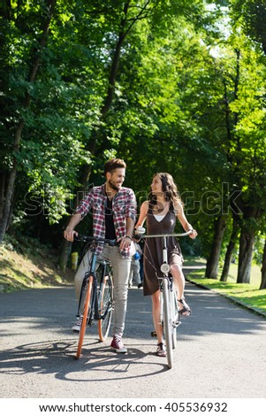 nice young couple with  bikes on a sunny summer day in an alley with green trees, admiring each other - stock photo