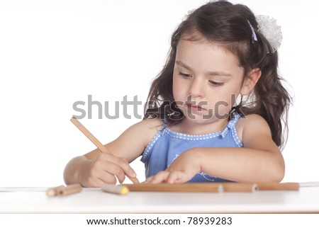 nice young girl drawing at table on a white