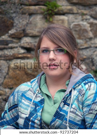 Nice young girl with glasses and blue Tshirt - stock photo