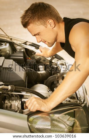 Nice young man repairing car, against green of summer park.