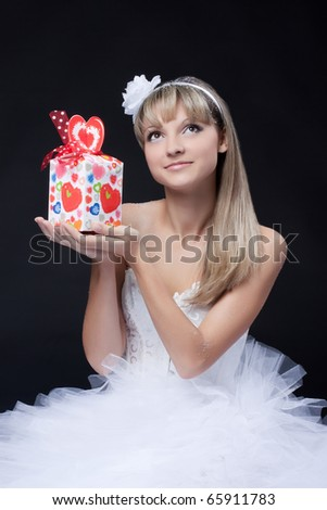 nice young woman in a white dress with a gift on a black background - stock photo