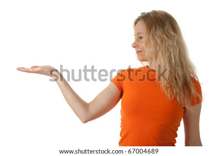 Nice young woman in orange t-shirt holding her hand palm up, ready to hold your product. - stock photo