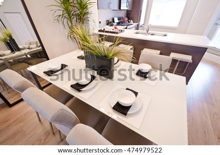 Nicely decorated and served living, lunch room table with the coffee, tea set and the kitchen at the back. Interior design.