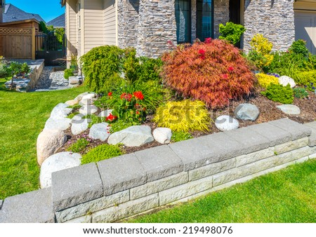 Nicely decorated colorful flowerbed and trimmed bushes at front yard lawn in front of the house. Landscape design. - stock photo