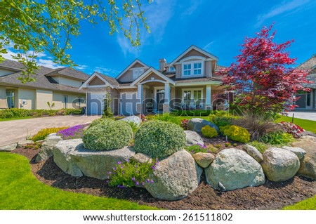 Nicely decorated front yard with flowers, stones and bushes as a decorative elements. Landscape design. - stock photo