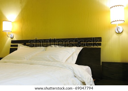 Nicely decorated hotel bedroom in the lamplight - stock photo