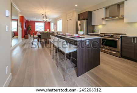 Nicely decorated kitchen counter table, iceland table and dining table and living room at the back. Interior design. - stock photo