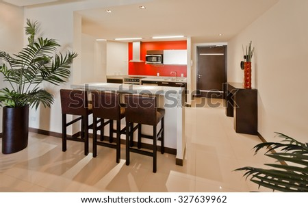 Nicely decorated kitchen counter table, iceland table, dining table and a modern kitchen at the back. Interior design.